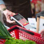 Uma pessoa utiliza o vale-alimentação como método de pagamento em um supermercado.